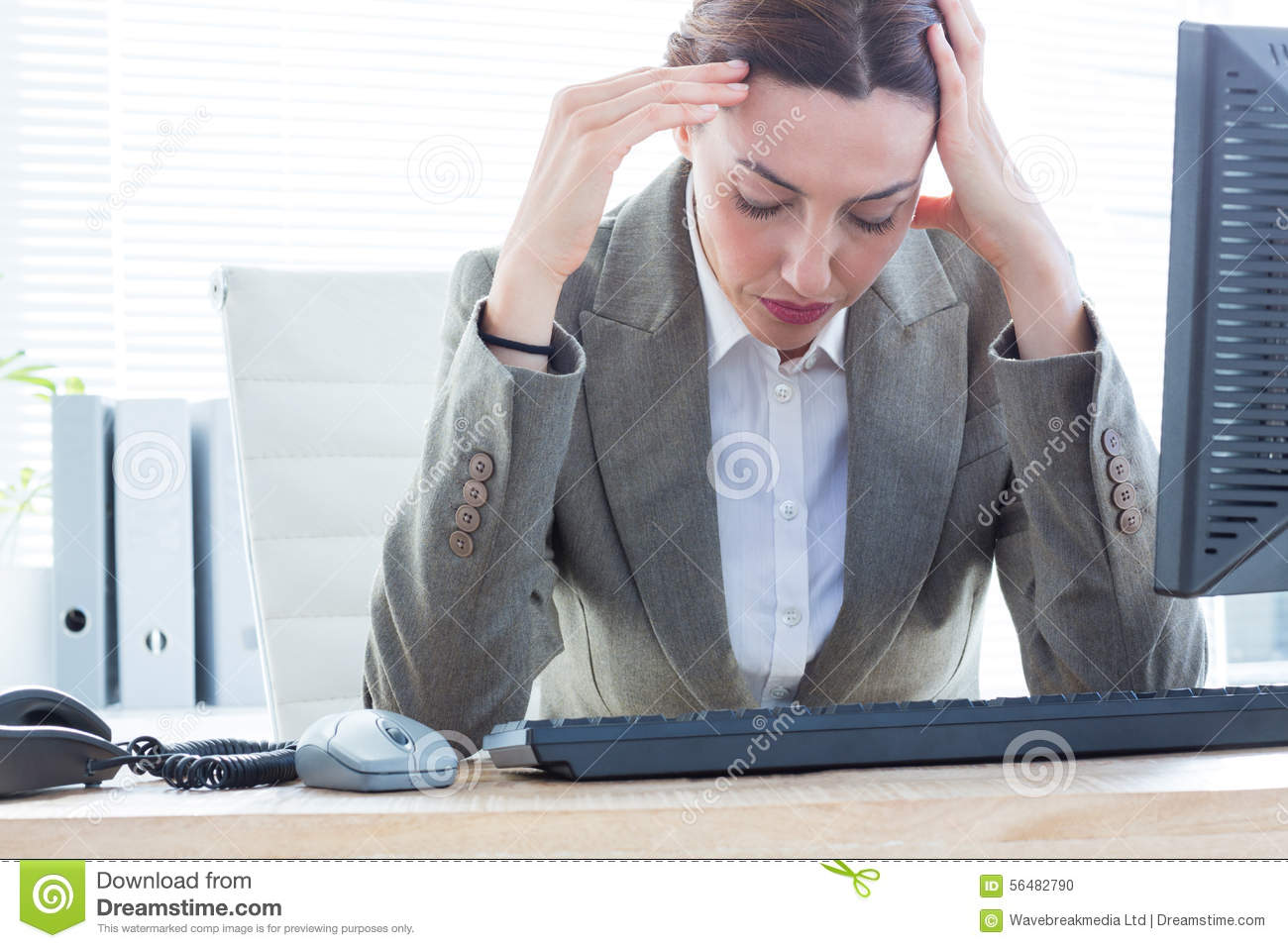 Upset business woman with head in hands in front of computer at office