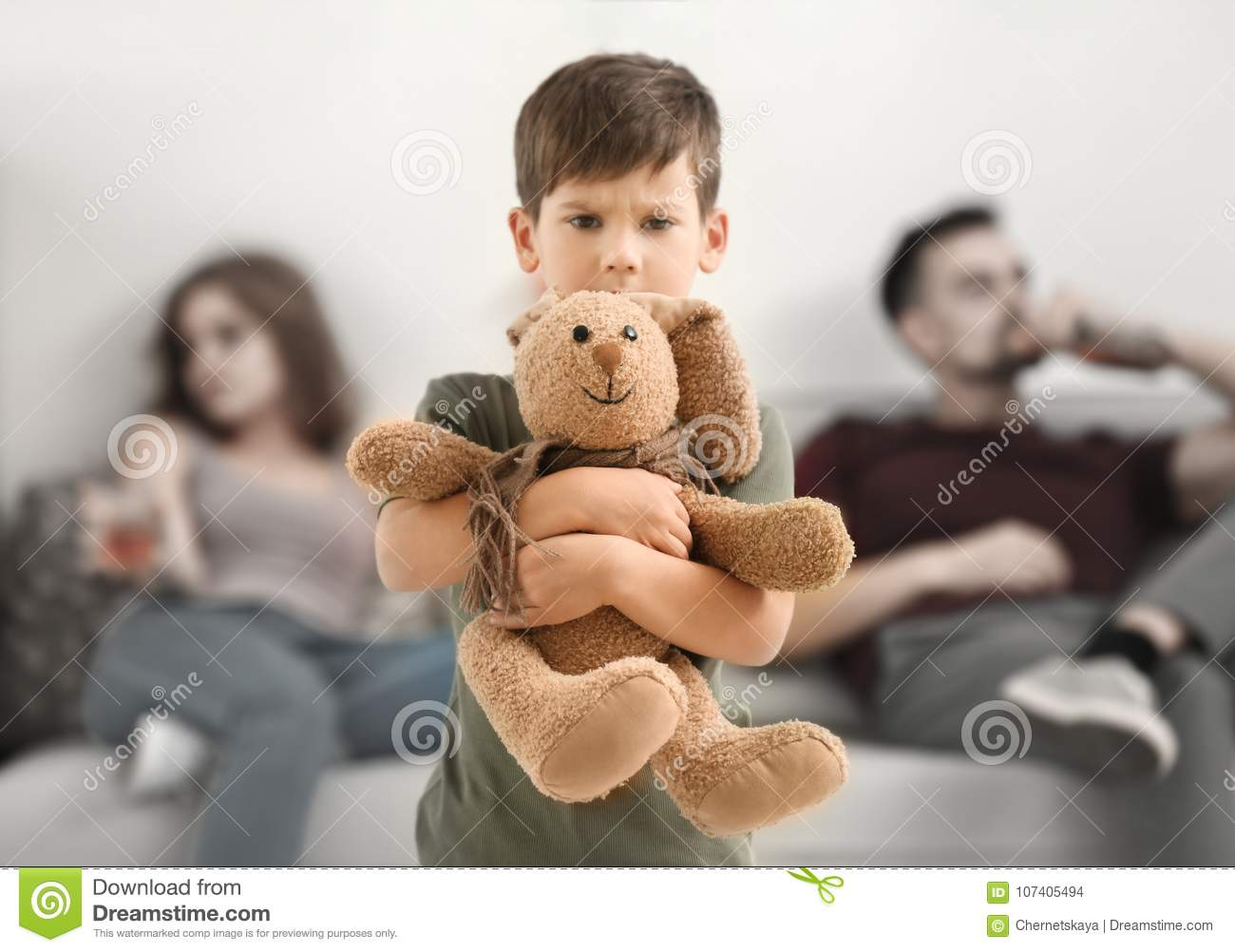 Upset little boy hugging toy bunny while his parents drinking alcohol