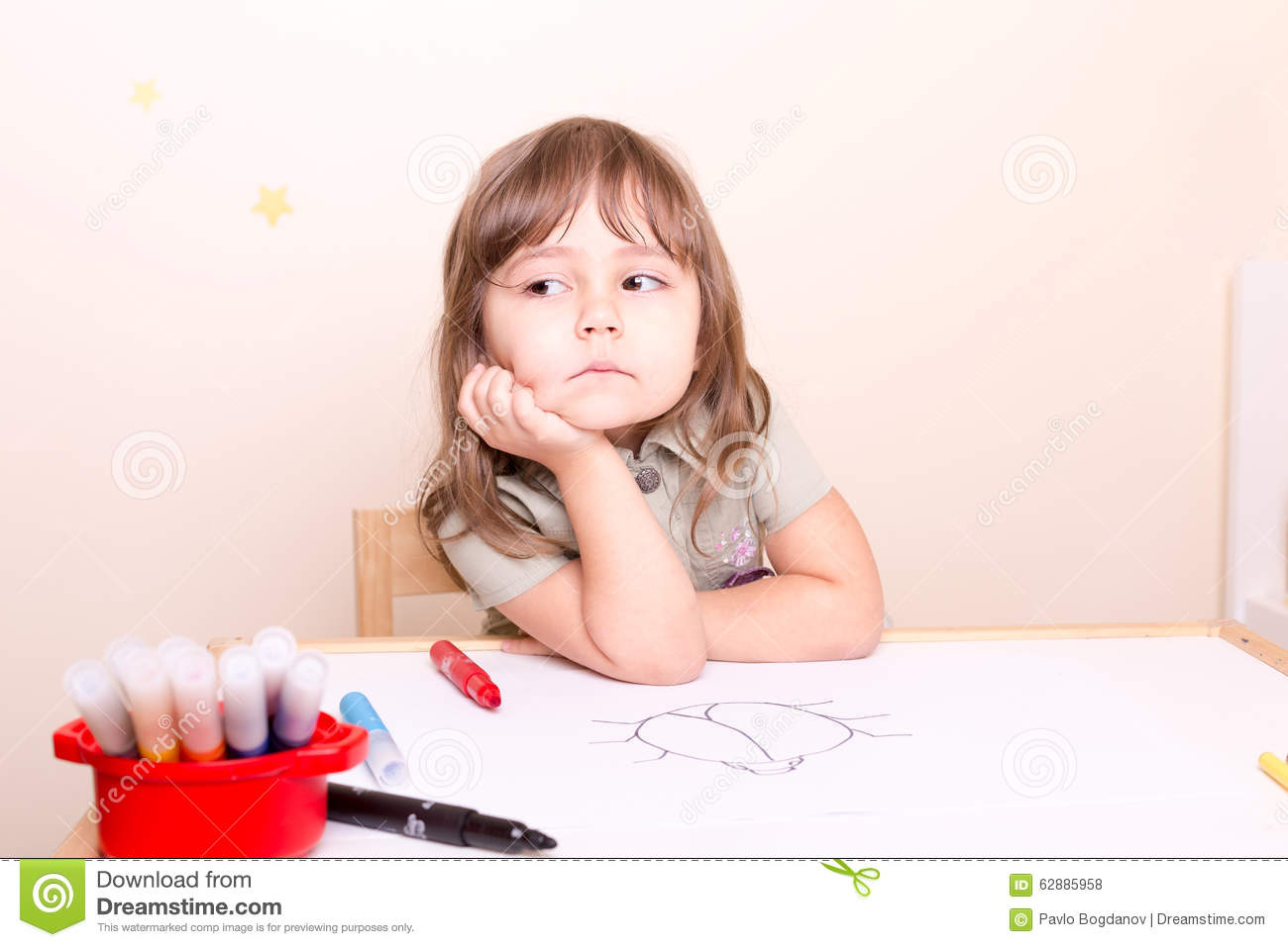 upset little girl sitting at the desk at school stock