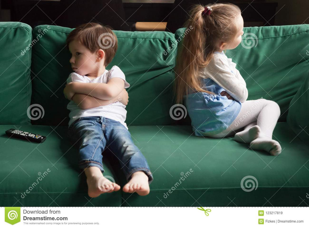 Upset Siblings Sitting On Sofa Ignoring Each Other After Fight