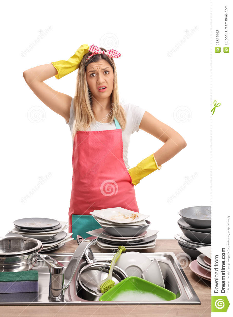 Upset young woman behind a sink filled with dirty plates
