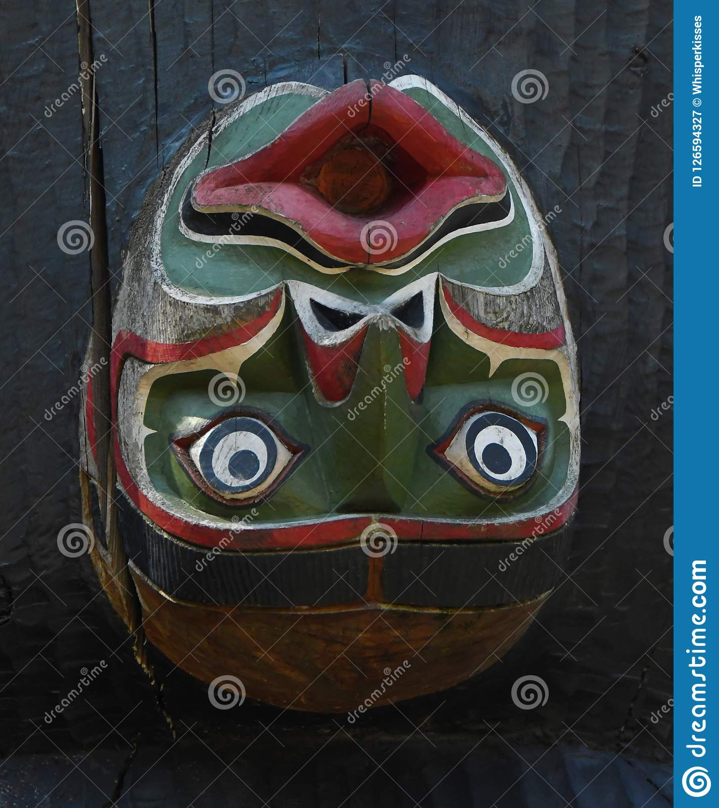 Upside down green and red totem face