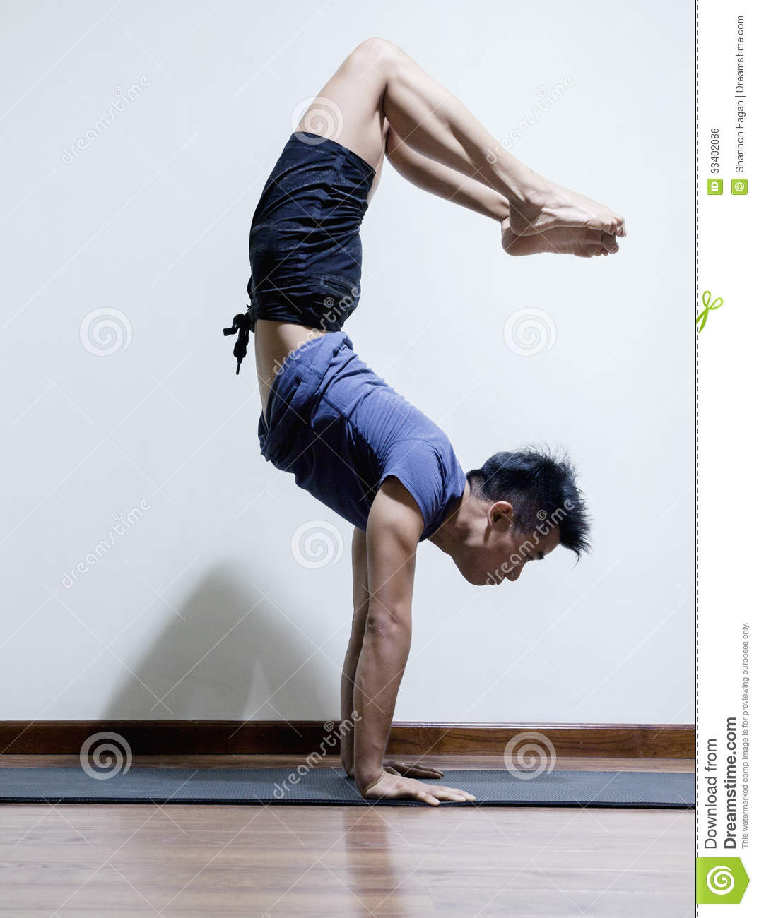 Upside Down Man Doing Yoga In A Yoga Studio Side View