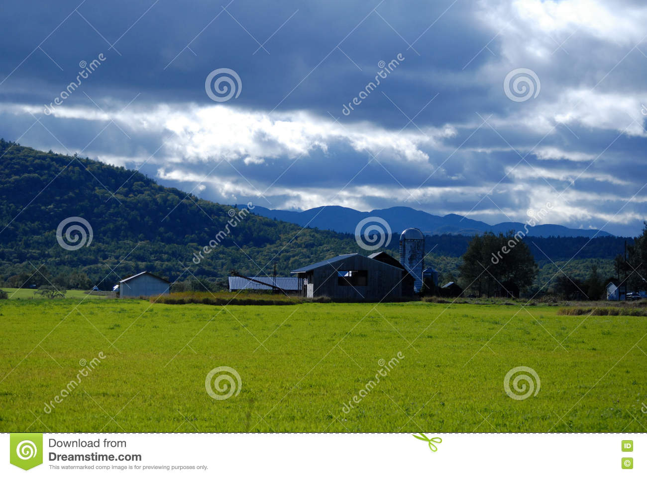 Upstate New York farm with tree covered Mountain with a blue clouded sky in autumn