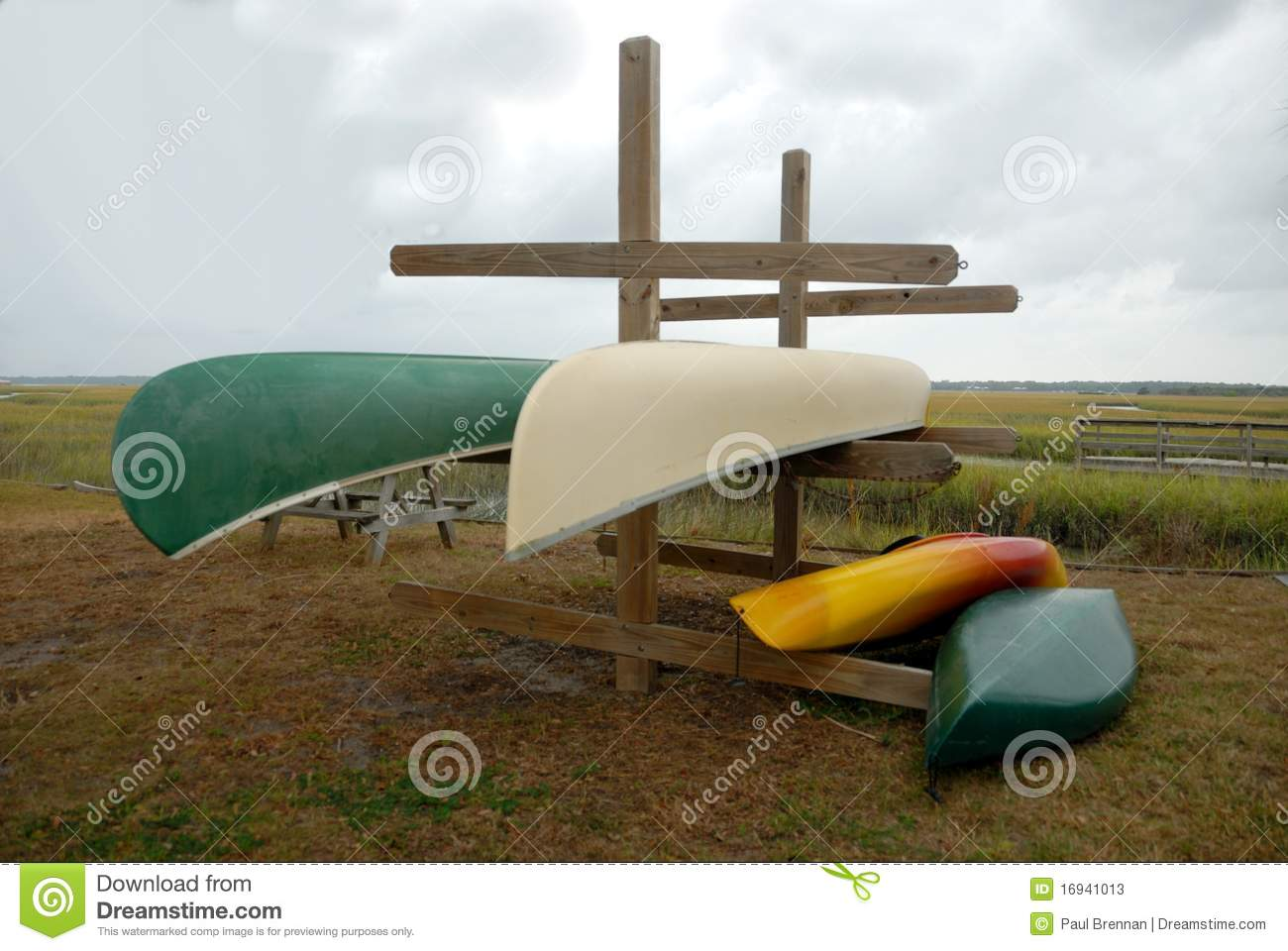 Colorful upturned canoes stored on wooden rack in countryside.