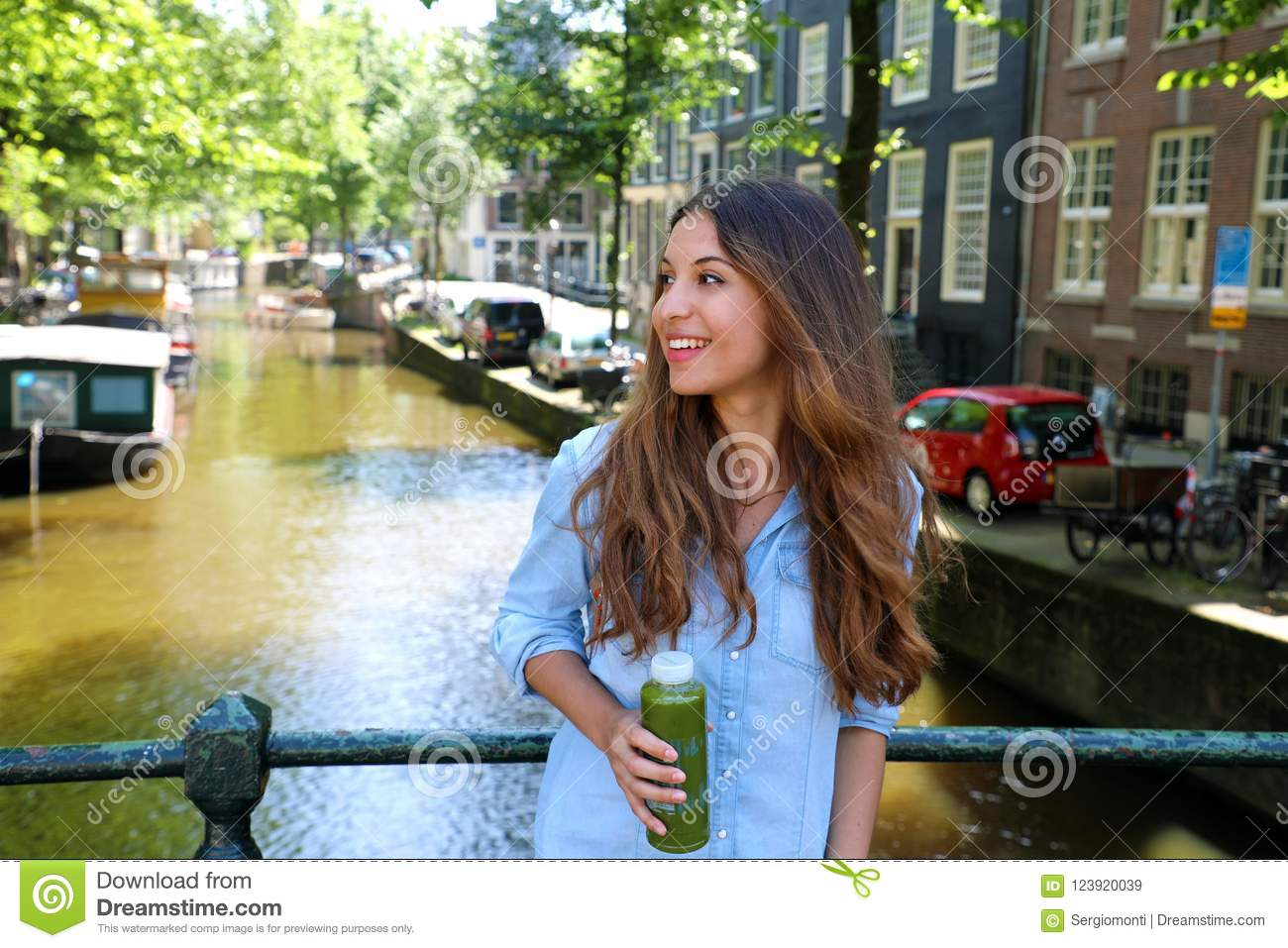 Urban city lifestyle hipster girl drinks green juice on Amsterdam canal, Netherlands. Healthy detox vegan diet with vegetable cold