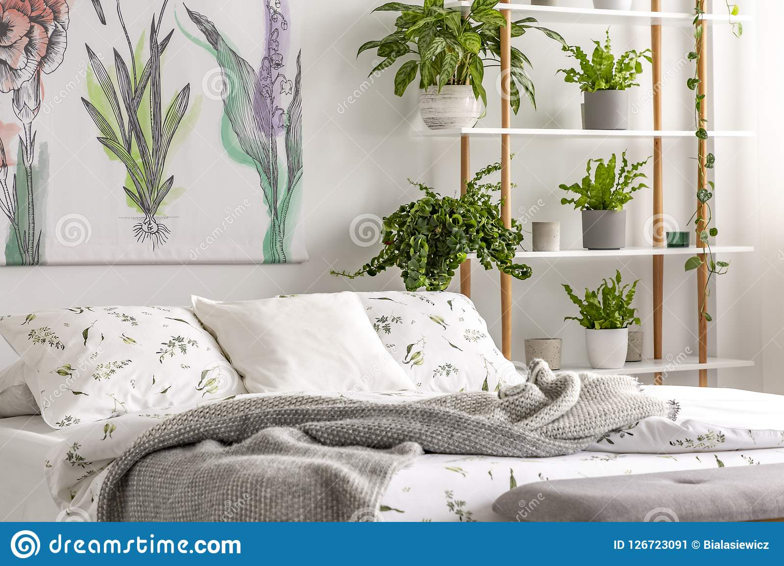 Urban jungle bedroom interior with plants in pots beside a bed dressed in organic cotton linen of white color with green print. Re