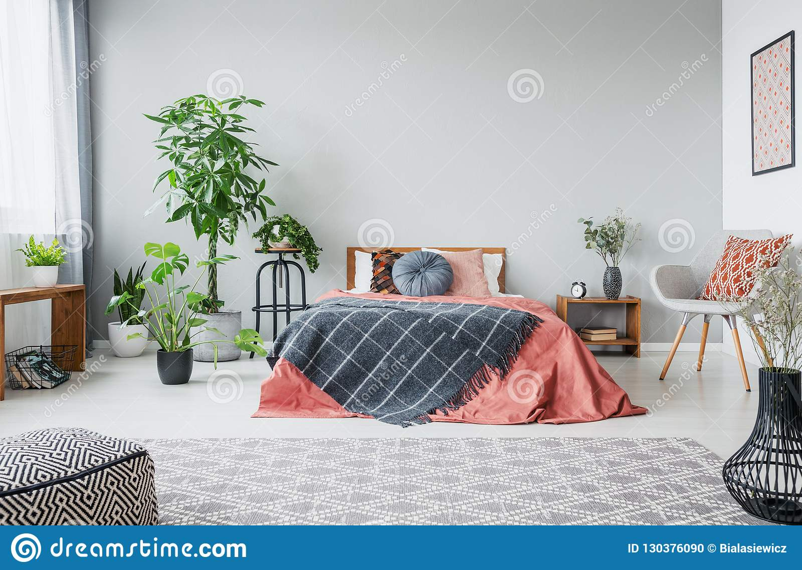 Urban jungle in modern bedroom with king size bed, comfortable grey armchair and patterned carpet