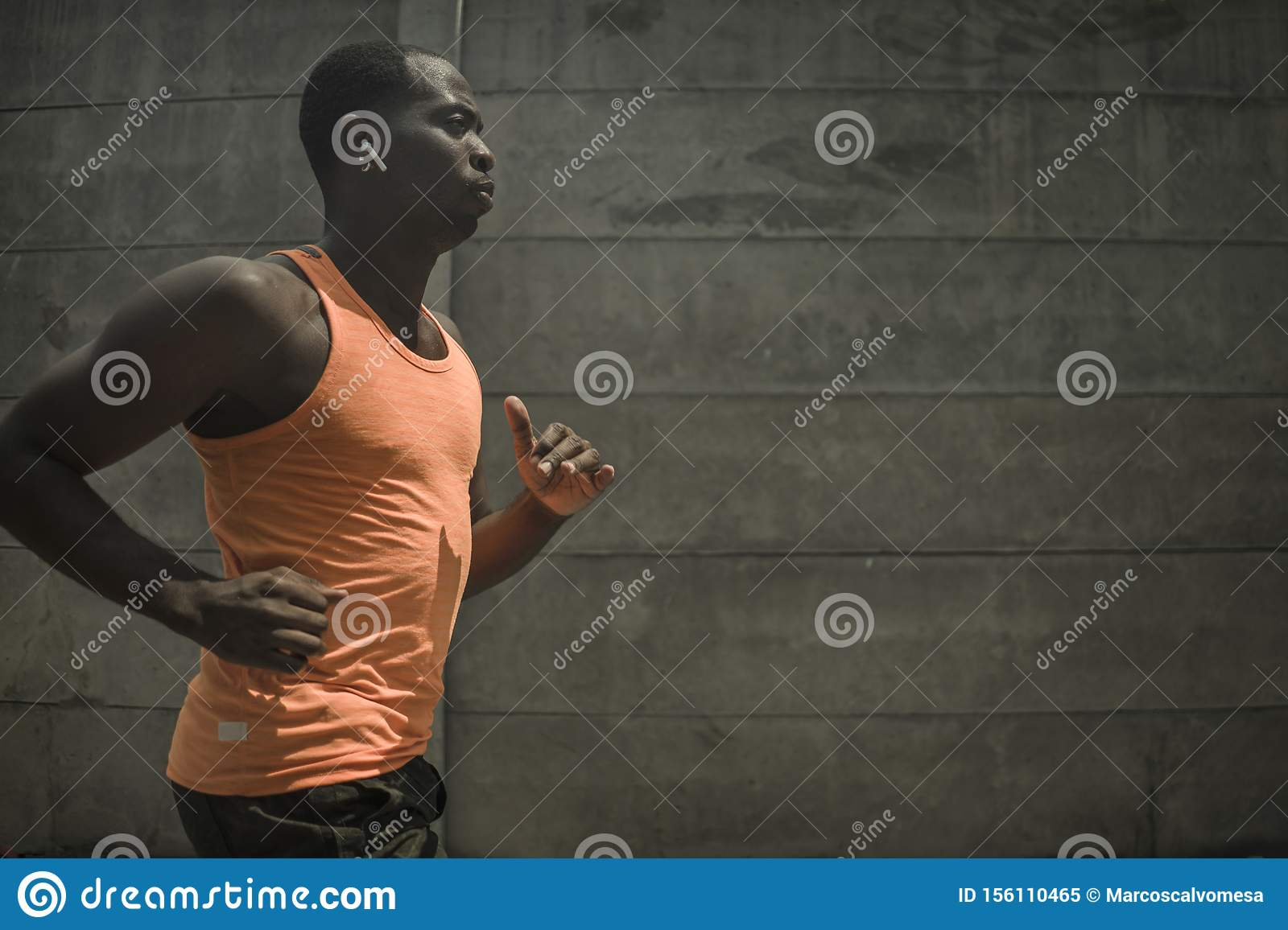 Urban runner workout . Young attractive and athletic black afro American man running outdoors on asphalt road training hard