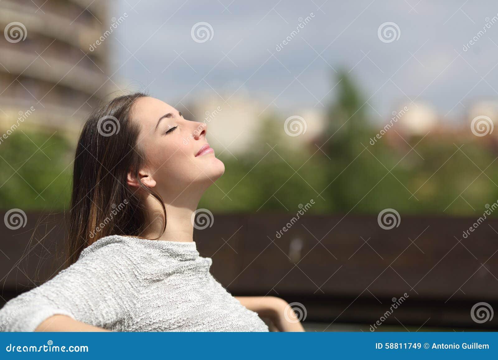 Urban woman breathing deep fresh air