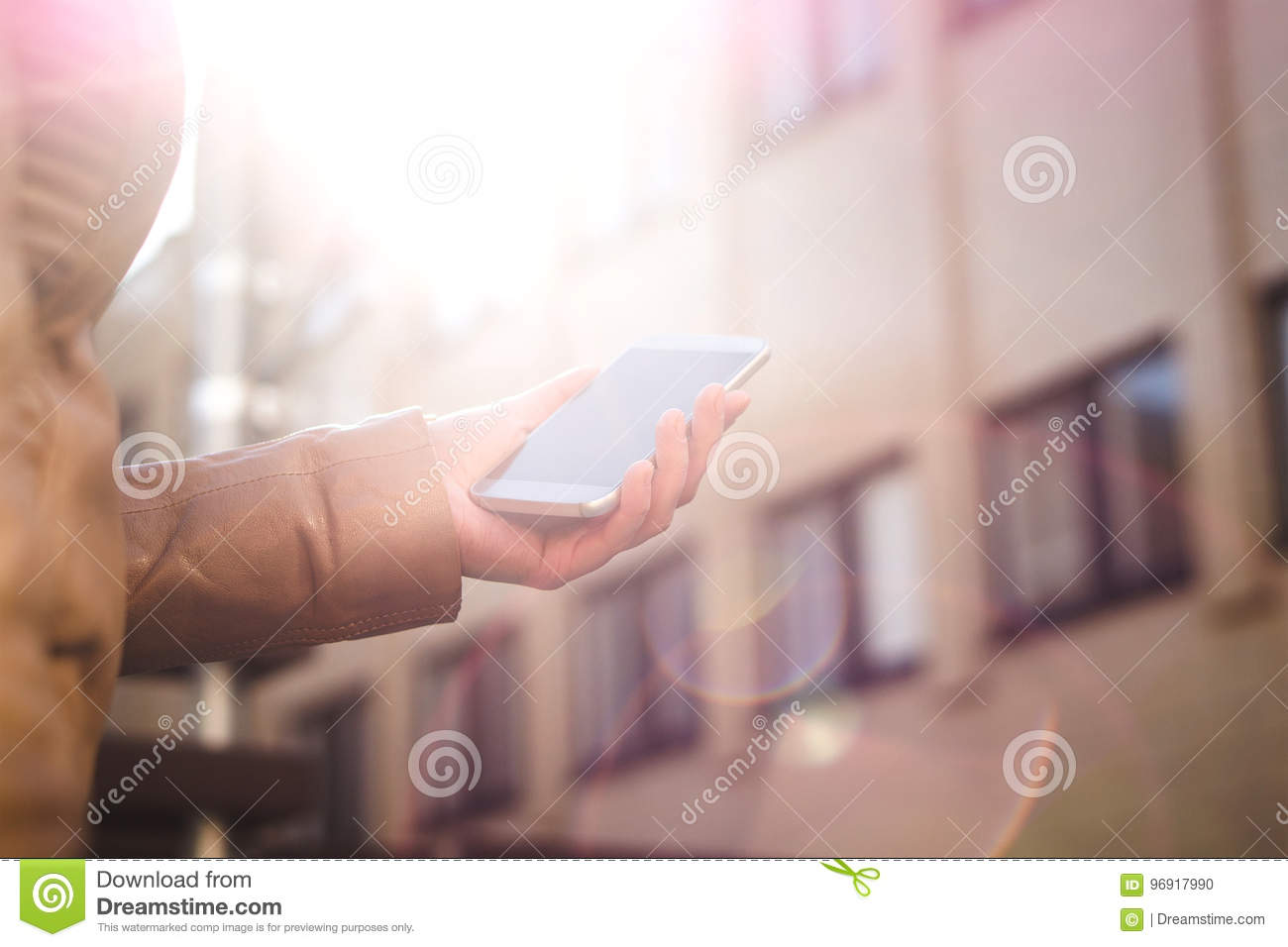 Urban woman holding smartphone and walking in sunshine. Modern and trendy lifestyle. Sunrise or sunset in the city centre.