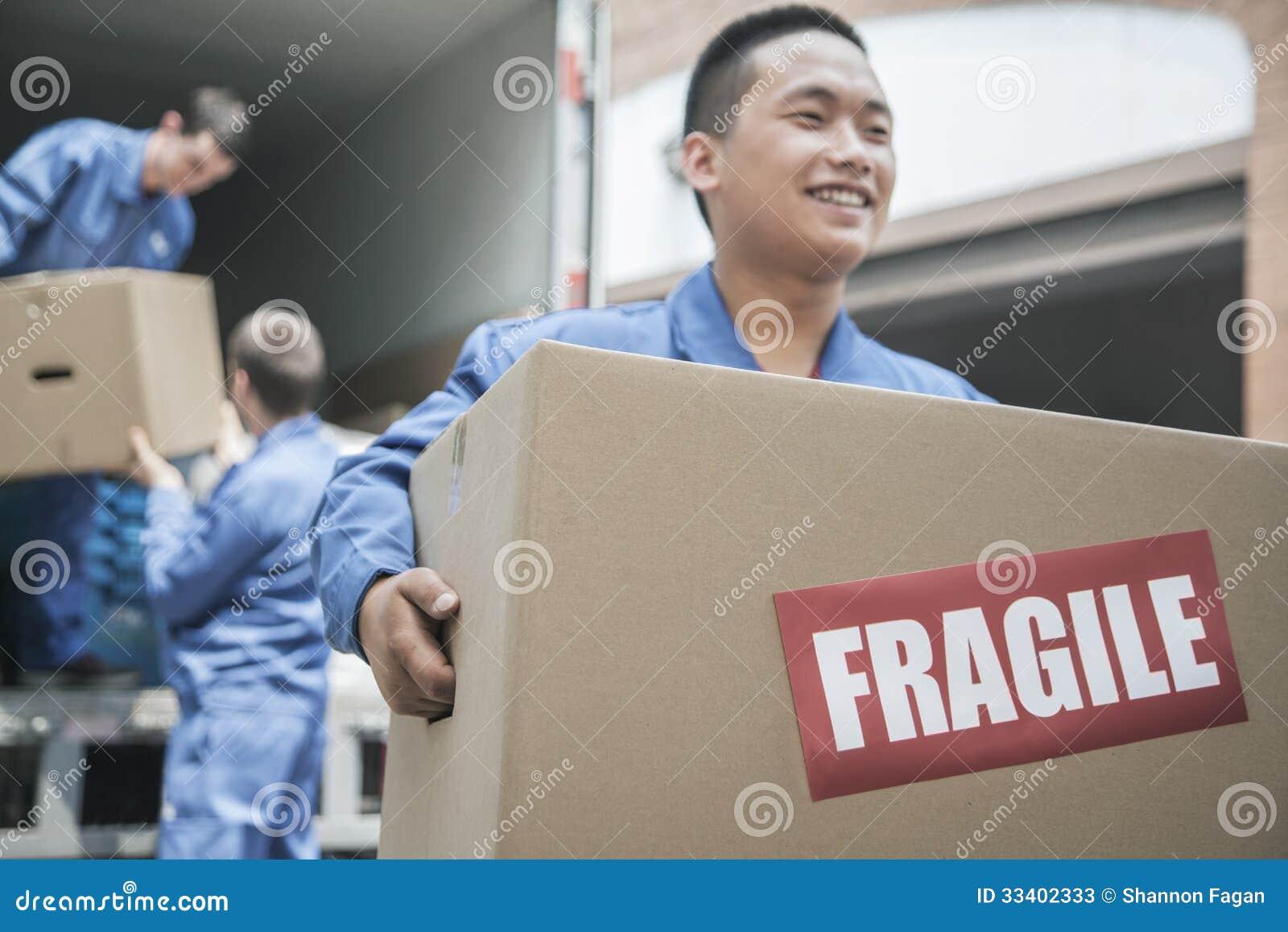 Urheber, die einen beweglichen Packwagen entladen und einen zerbrechlichen Kasten tragen