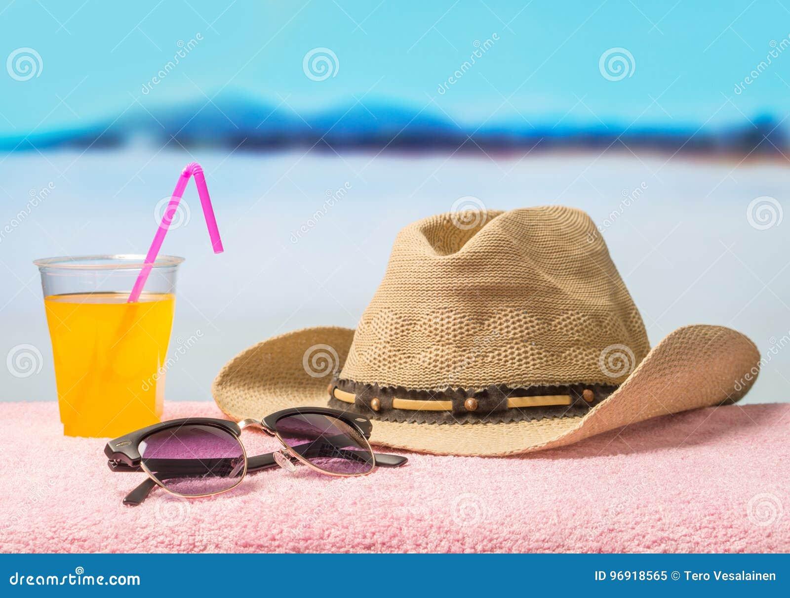 Urlaubsabenteuer- und Sommerferienkonzept mit wesentlicher Ausrüstung Geströmter Hut, Sonnenbrille und gelbes köstliches Getränk