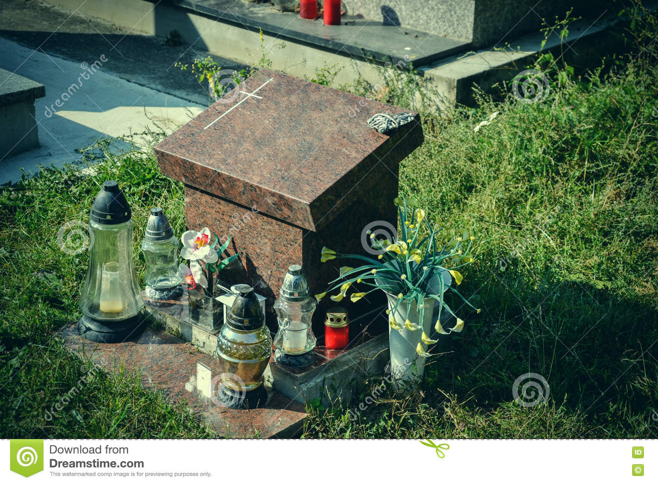 Urn grave with cross on traditional cemetery. Votive candles lantern and flowers on tomb stones in graveyard. All Saints  Day