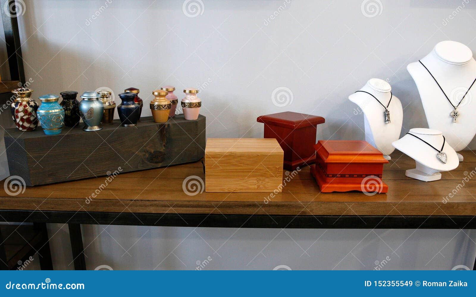 Urnas adultas de la cremación en una superficie de madera
