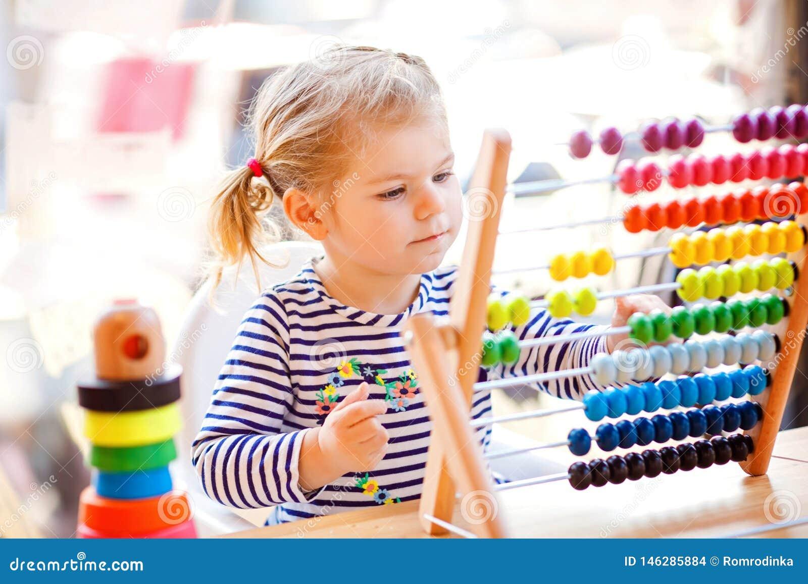 Urocza śliczna piękna mała berbeć dziewczyna bawić się z edukacyjnym drewnianym tęczy zabawki ostrosłupem i kontuaru abakusem