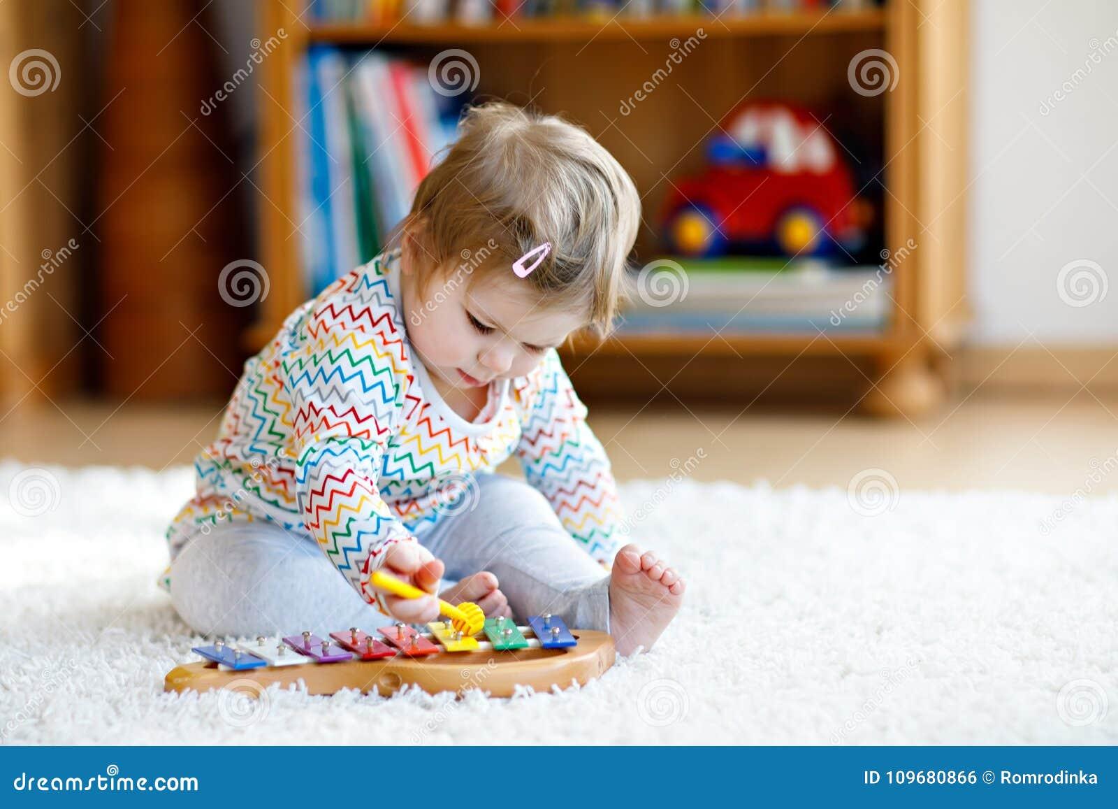 Urocza śliczna piękna mała dziewczynka bawić się z edukacyjną drewnianą muzyką bawi się w domu lub pepiniera Berbeć z