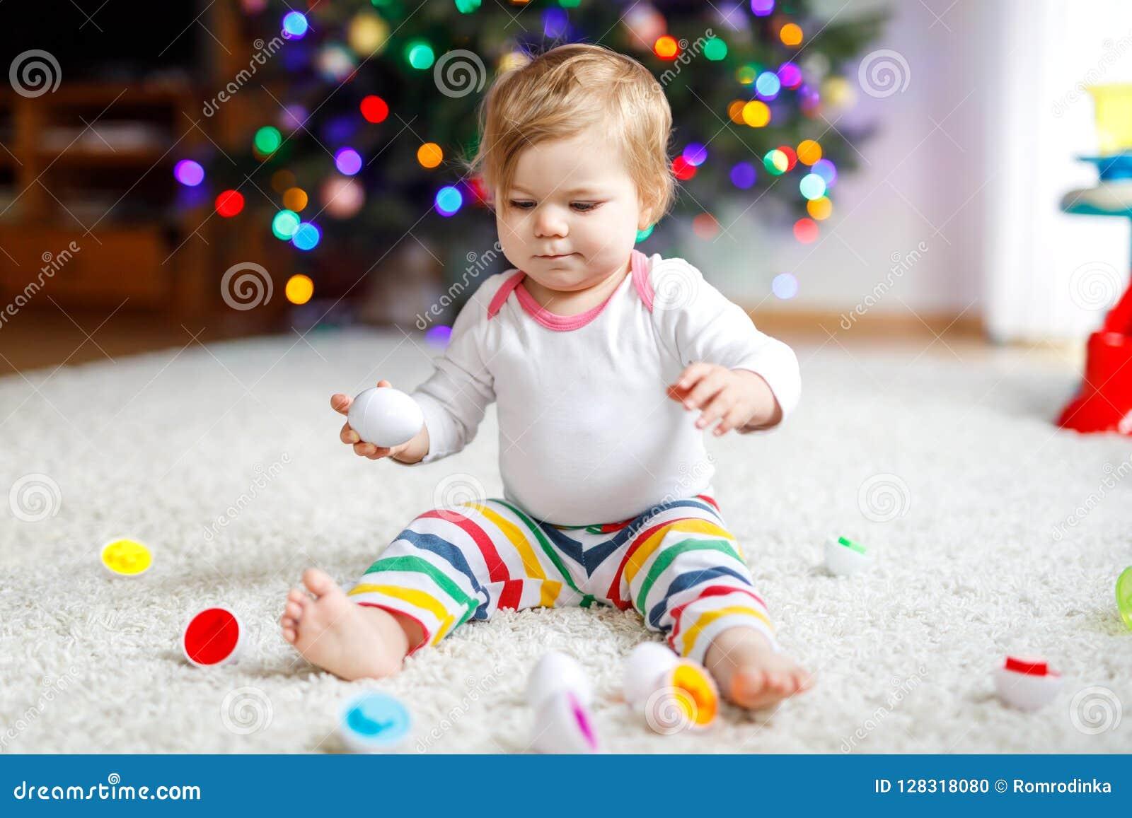 Urocza śliczna piękna mała dziewczynka bawić się z edukacyjną kolorową kształt brakarki zabawką