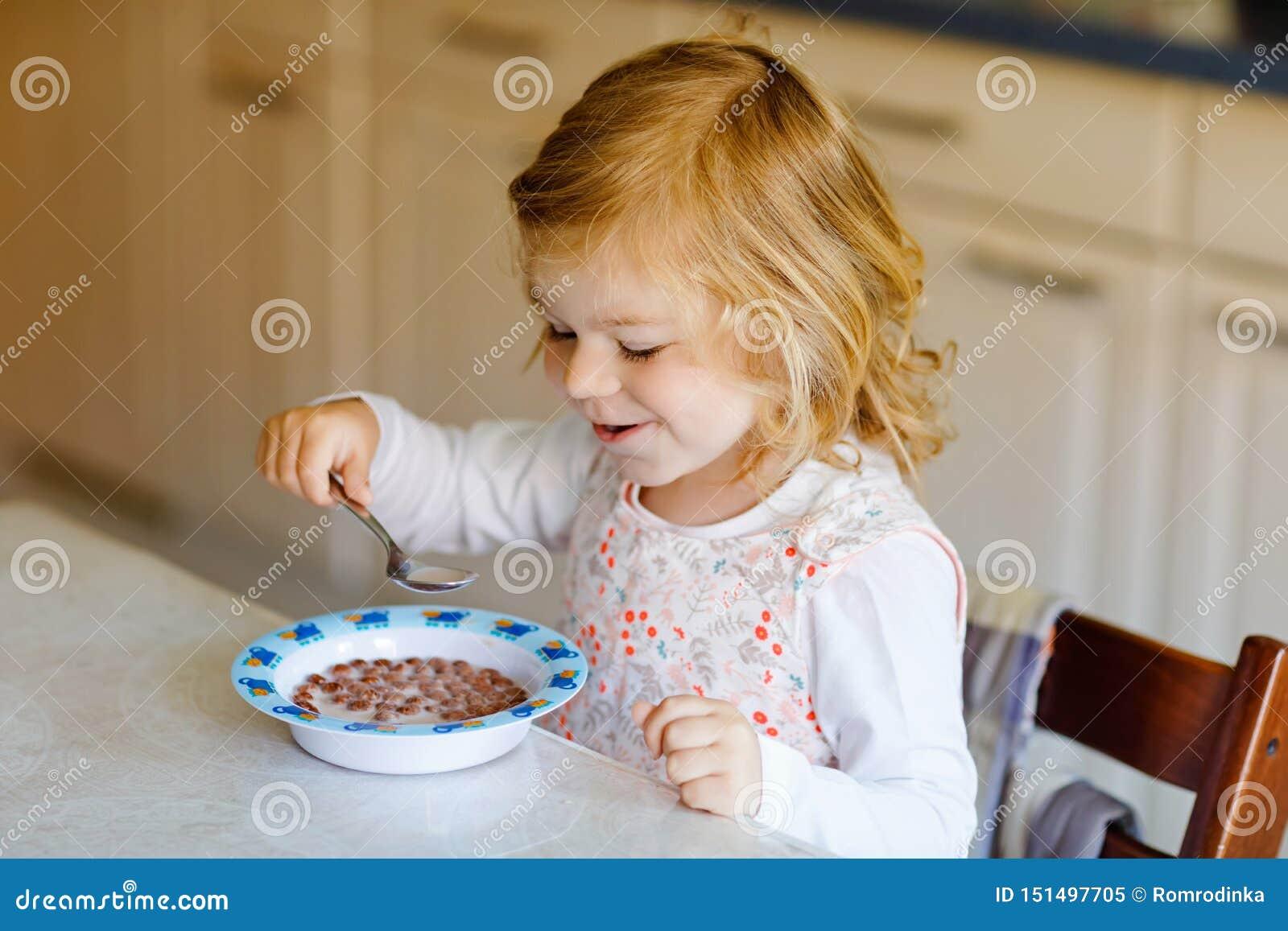 Urocza berbeć dziewczyna je zdrowego zboża z mlekiem dla śniadaniowego Ślicznego szczęśliwego dziecka dziecka w kolorowy ubrań si