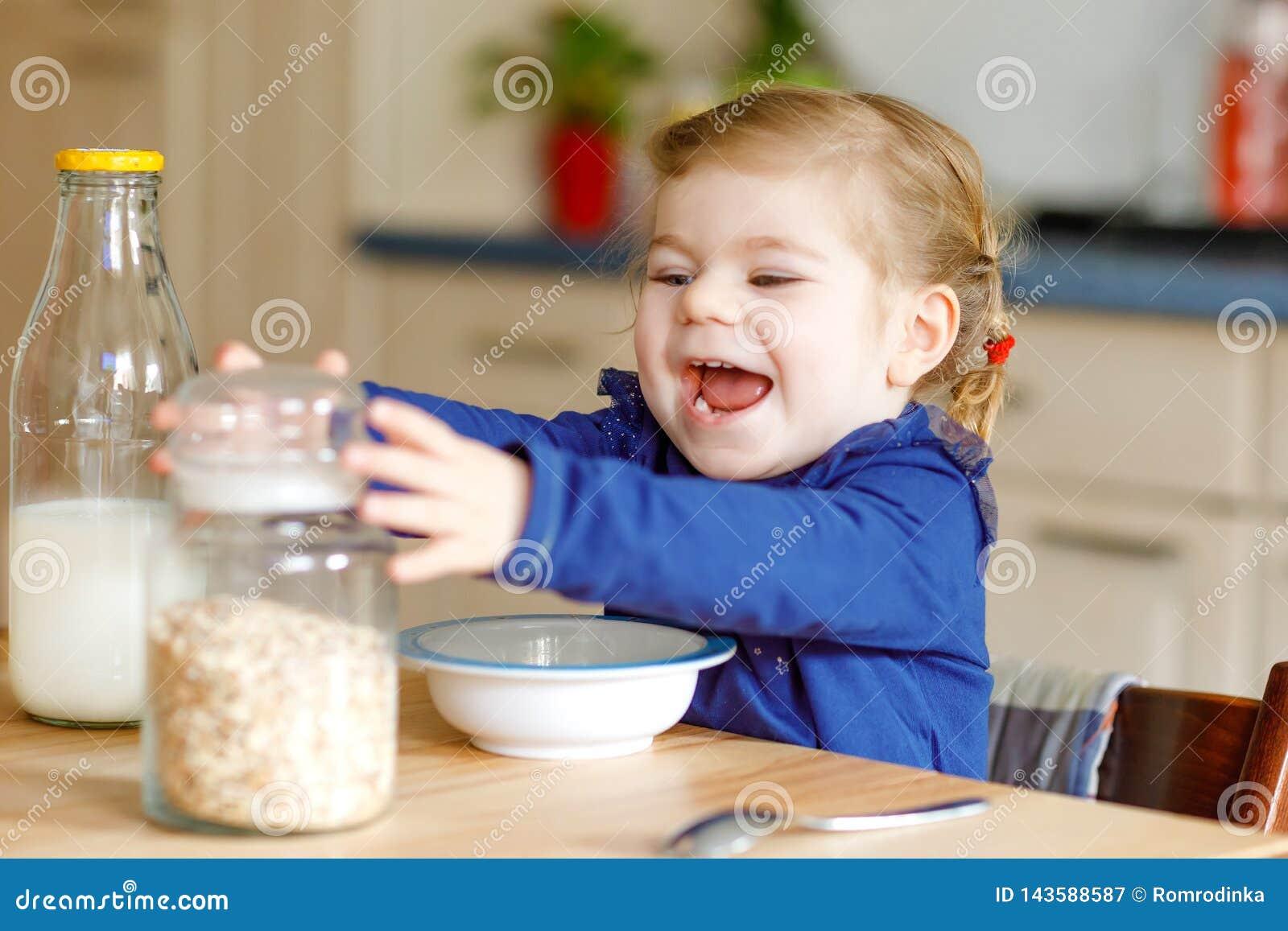 Urocza berbeć dziewczyna je zdrowych oatmeals z mlekiem dla śniadaniowego Ślicznego szczęśliwego dziecka dziecka w kolorowy ubrań
