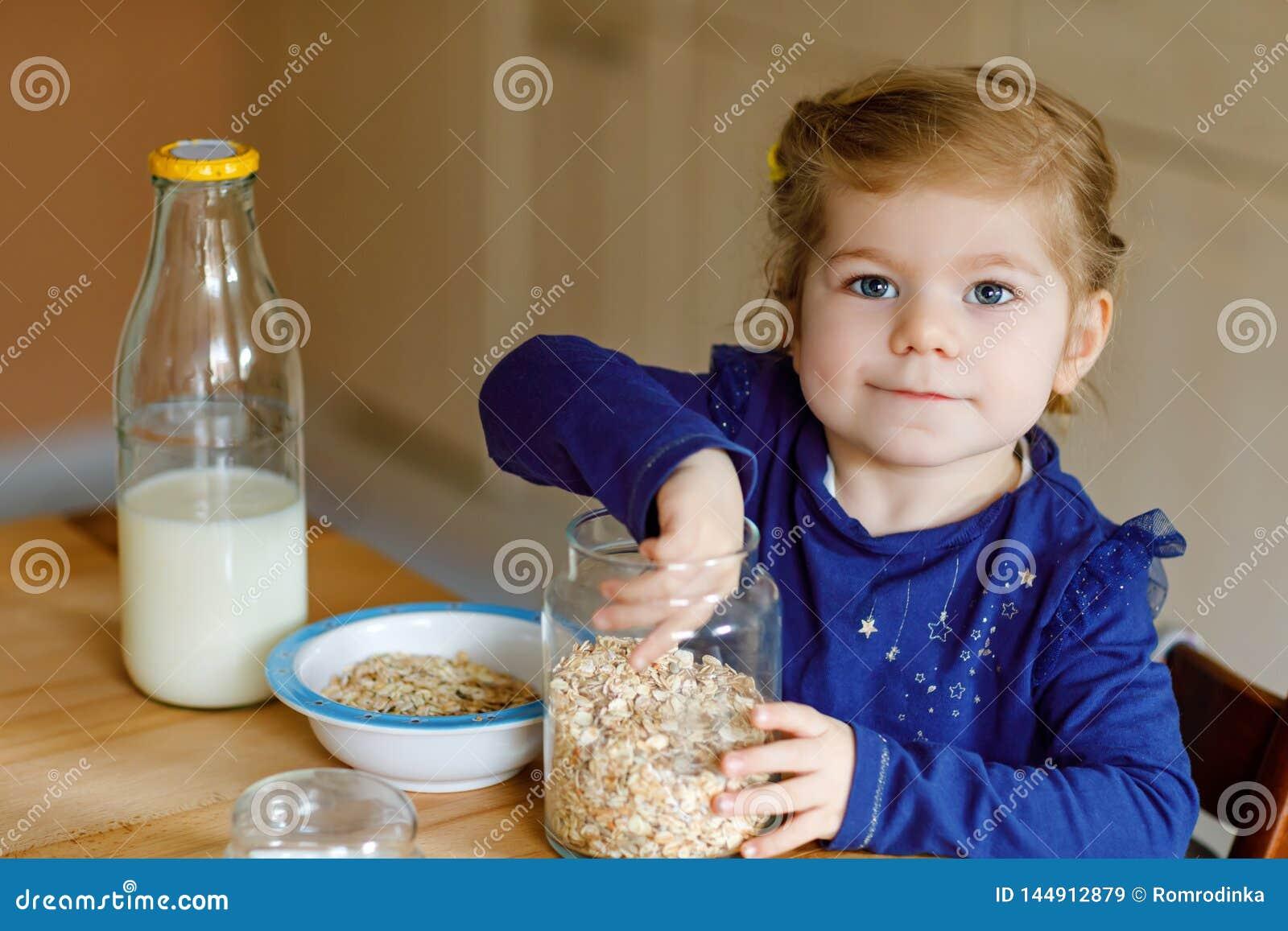 Urocza berbe? dziewczyna je zdrowych oatmeals z mlekiem dla ?niadaniowego ?licznego szcz??liwego dziecka dziecka w kolorowy ubra?