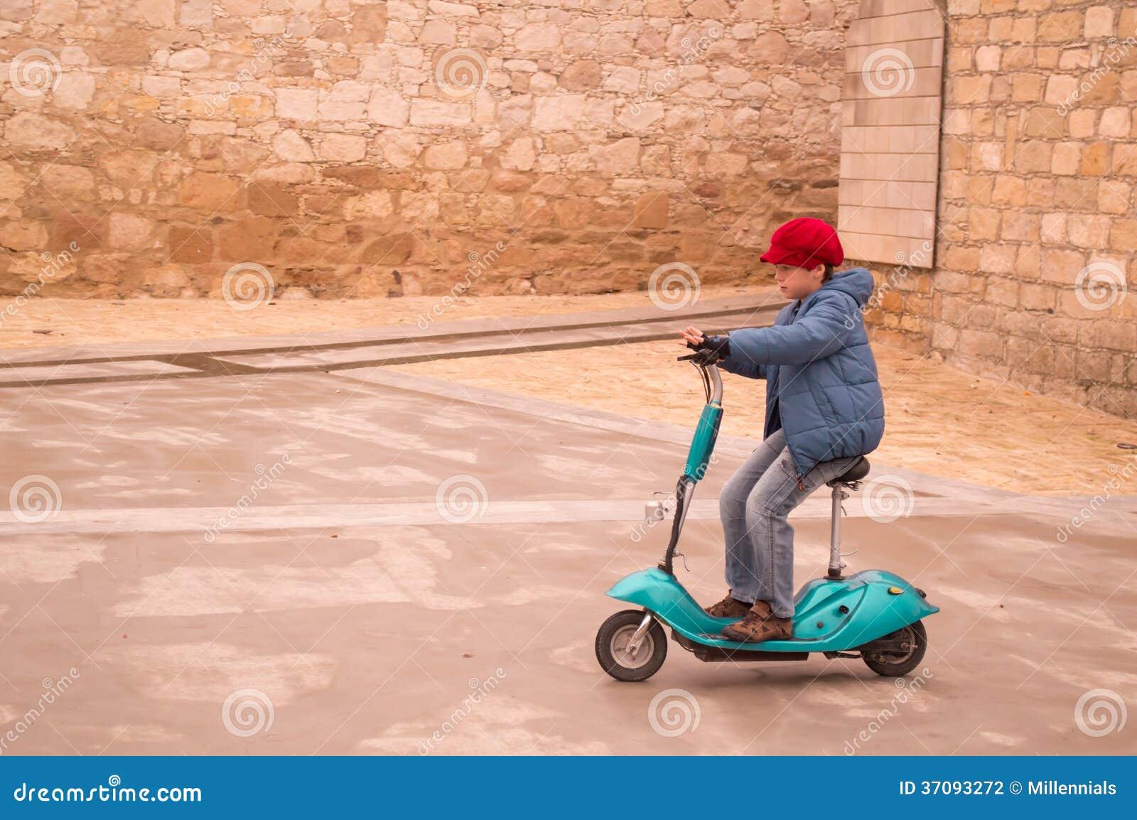 Download Urocza Chłopiec Jedzie Elektryczną Hulajnoga Zdjęcie Stock - Obraz złożonej z zimno, elektryczność: 37093272