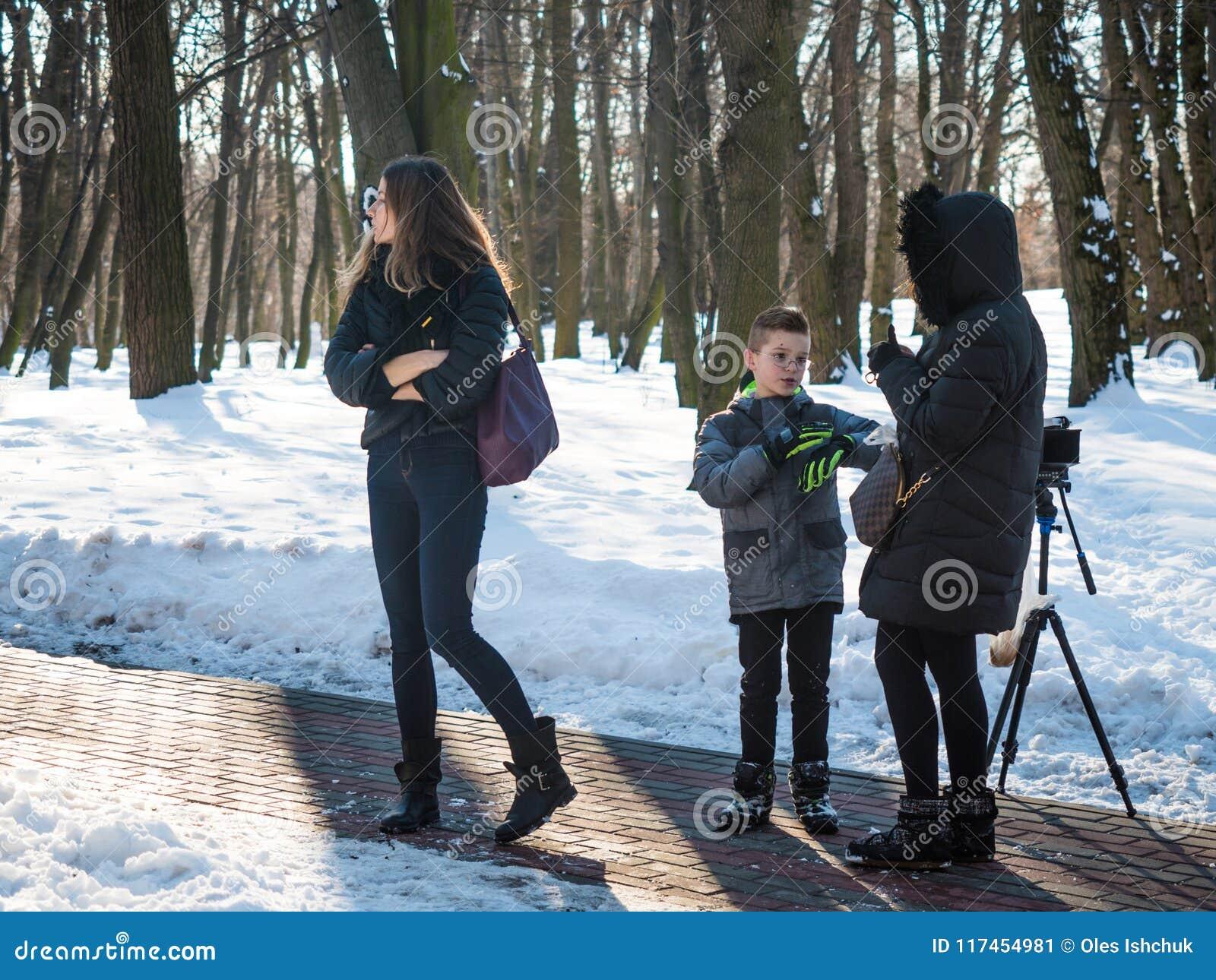 Urocza chłopiec modela rozmowa z producentem w zima parku, zakulisowym