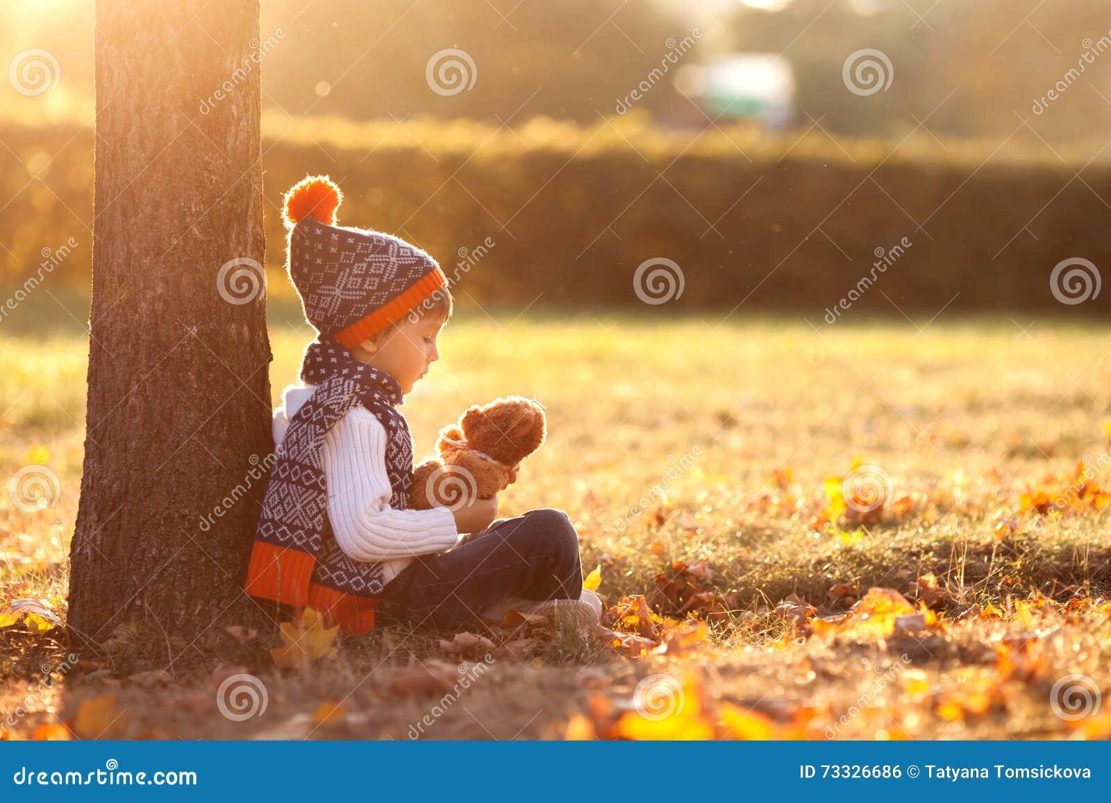Urocza chłopiec z misiem w parku na jesień dniu