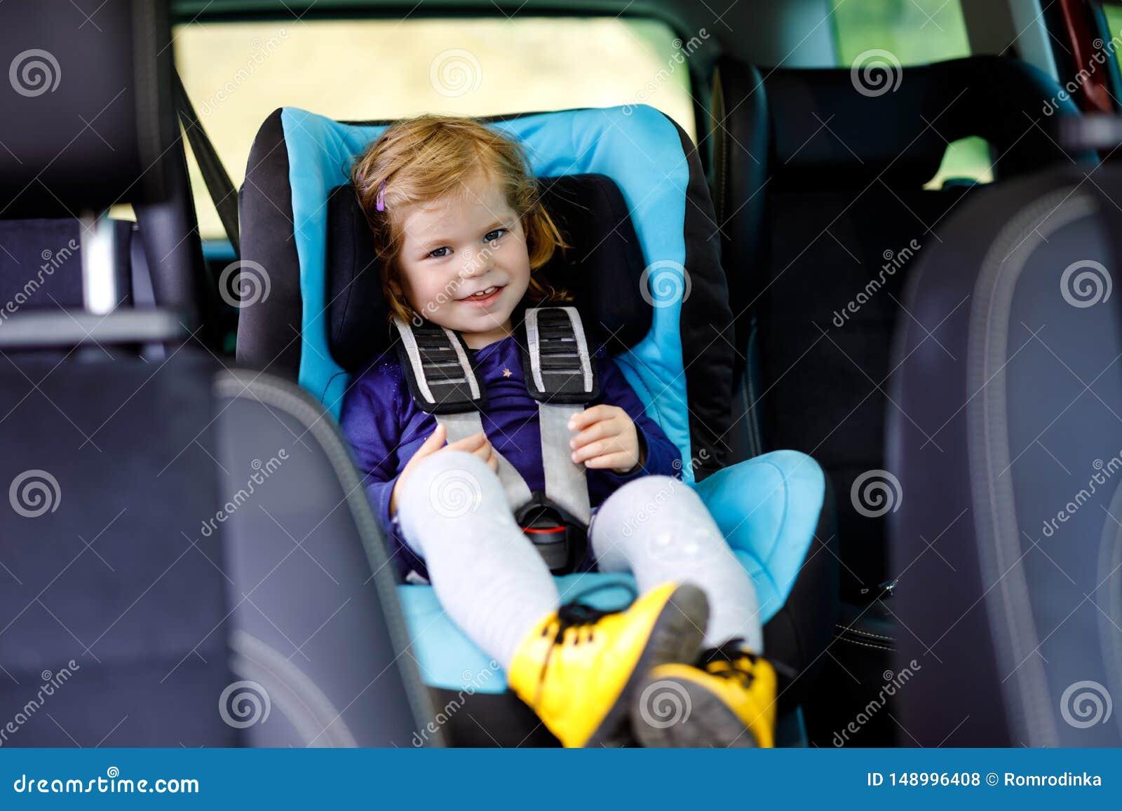 Urocza dziewczynka siedzi w samochodowym zbawczym siedzeniu z niebieskimi oczami Berbecia dziecko i?? na rodzinnych wakacjach i j