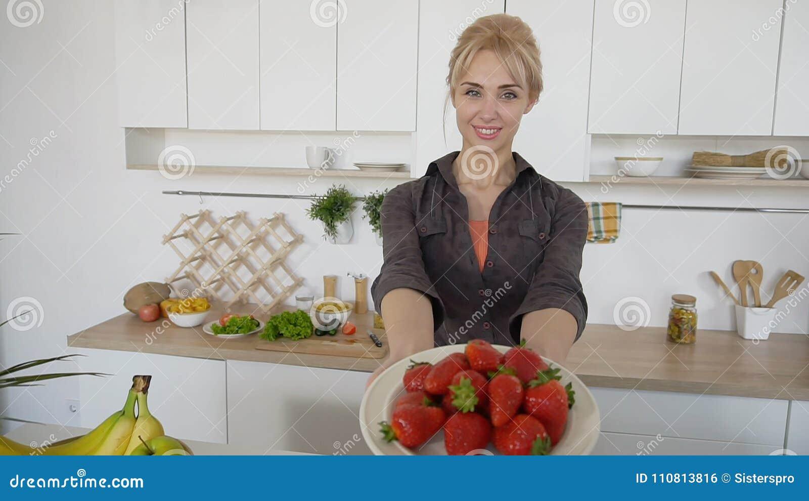 Urocza kobieta pozuje i ono uśmiecha się przy kamerą z talerzem dojrzały st