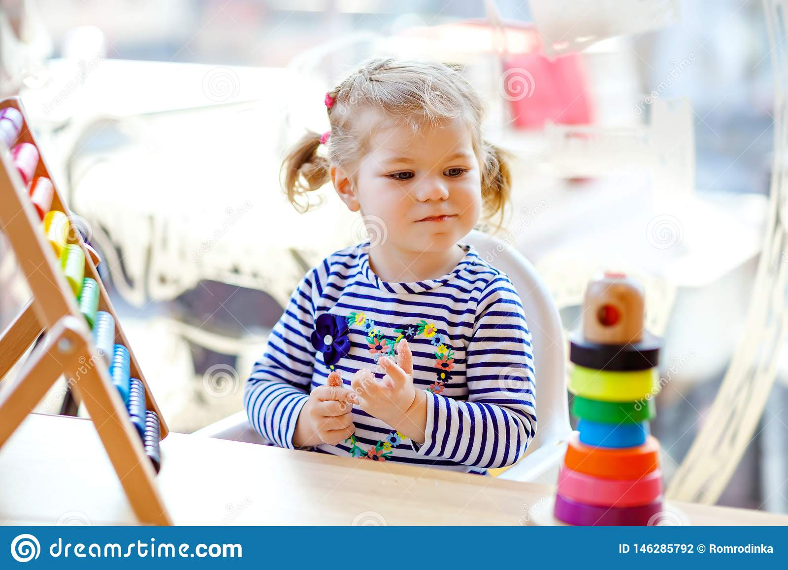 Urocza ?liczna pi?kna ma?a berbe? dziewczyna bawi? si? z edukacyjnym drewnianym t?czy zabawki ostros?upem i kontuaru abakusem