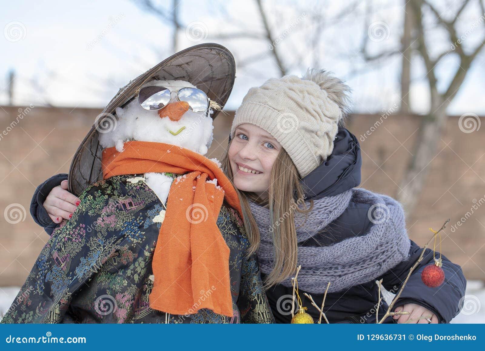 Urocza młoda dziewczyna z bałwanem w pięknym zima parku Zim aktywność dla dzieci