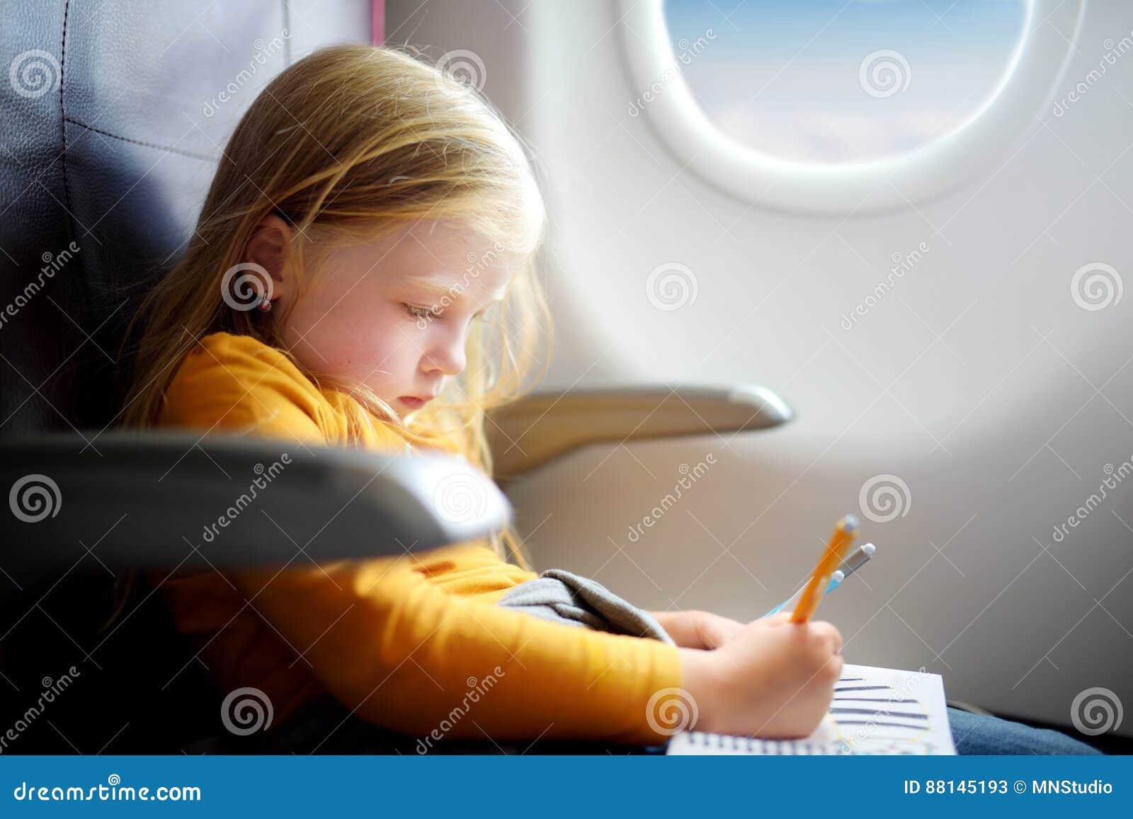 Urocza mała dziewczynka podróżuje samolotem Dziecka obsiadanie samolotu rysunkiem i okno obrazek z poradą pisze