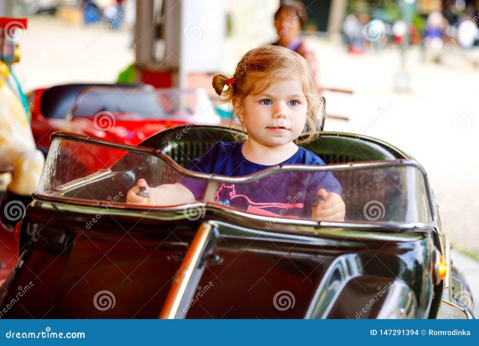 Urocza ma?a berbe? dziewczyny jazda na ?miesznym samochodzie na ronda carousel w parku rozrywkim Szcz??liwy zdrowy dziecka dzieck