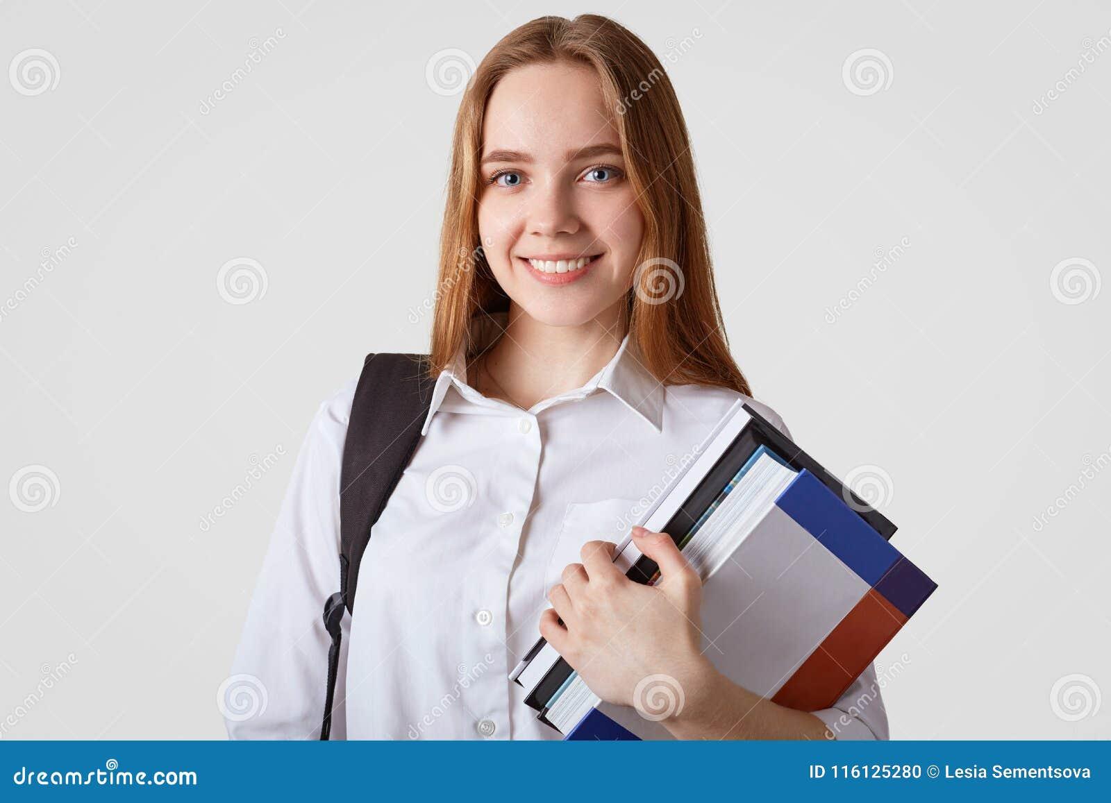 Urocza szkolna dziewczyna z niebieskimi oczami, błyszczy uśmiech, jest ubranym elegancką białą koszula, niesie książki i plecak,