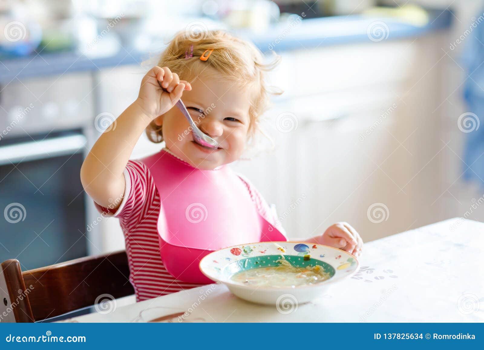 Uroczy dziewczynki łasowanie od łyżkowej jarzynowej kluski polewki jedzenia, dziecka, karmienia i rozwoju pojęcie, słodki paker