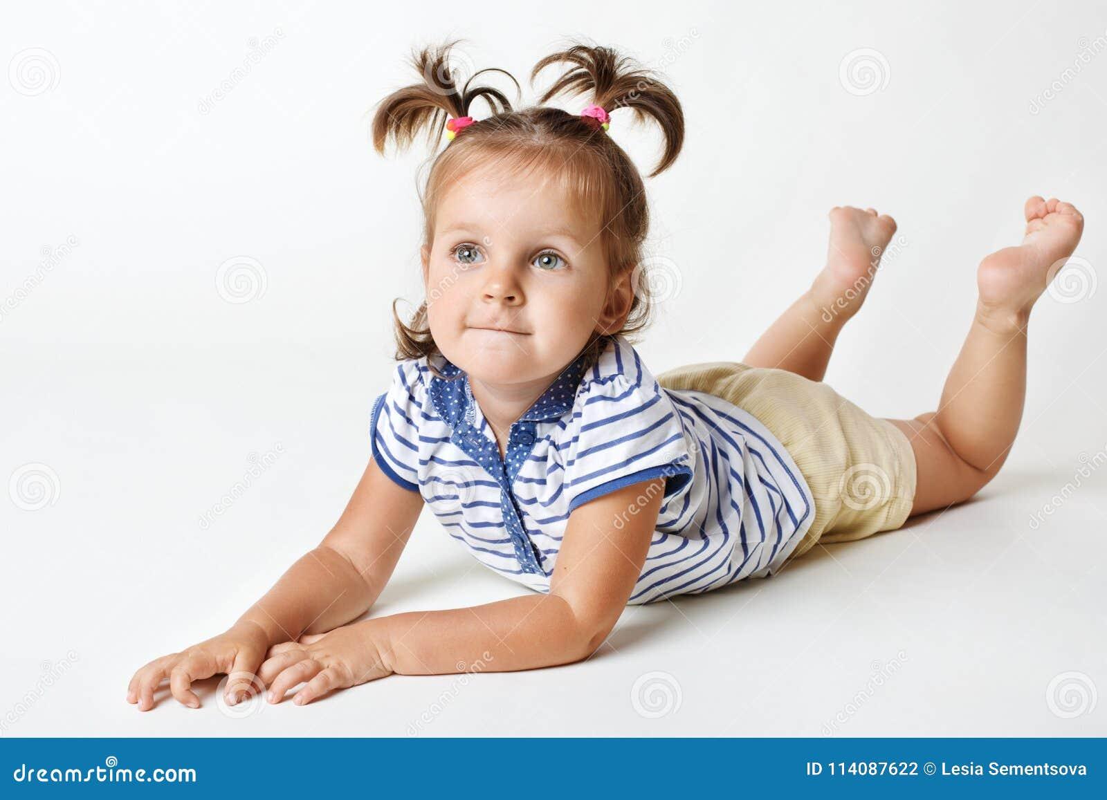 Uroczy mały żeński dzieciak z atrakcyjnym spojrzeniem, marzycielski wyrażenie, dwa śmiesznego konika ogonu, podwyżek nogi upwards