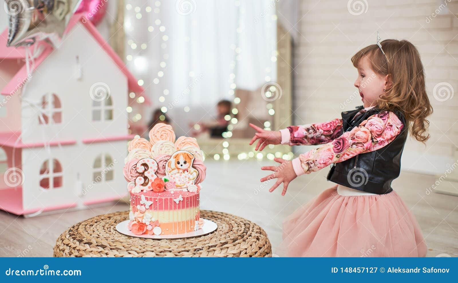 Urodzinowy tort dla 3 rok dekoruj?cych z motylami, piernikow? figlark? i numerowymi trzy z lodowaceniem, beza jasnor??owa wewn?tr