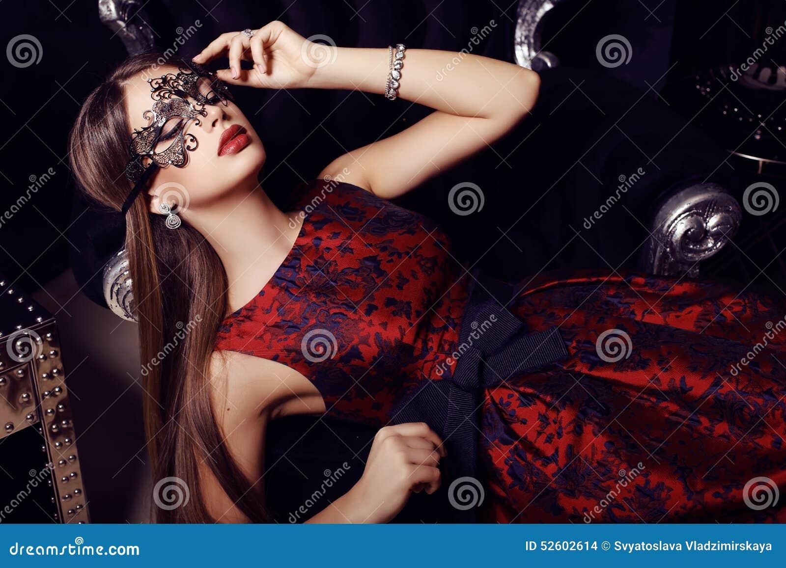 Ursnygg kvinna med mörkt hår i elegant klänning och maskering
