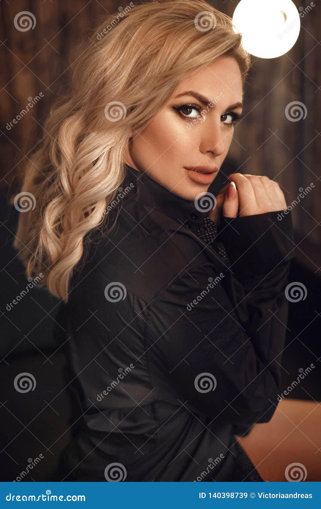 Ursnygg modell Blond kvinnastående i svart skjorta Trendig flicka med skönhetmakeup och stil för lockigt hår som poserar i trä