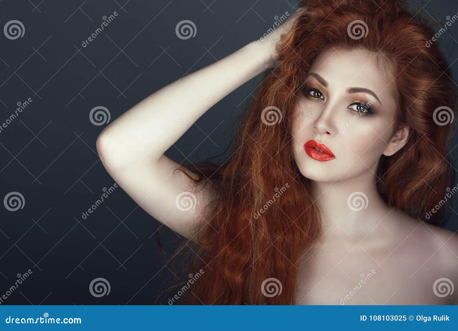 Ursnygg röd hövdad kvinna med det härliga sminket som rymmer hennes hand i hennes hår