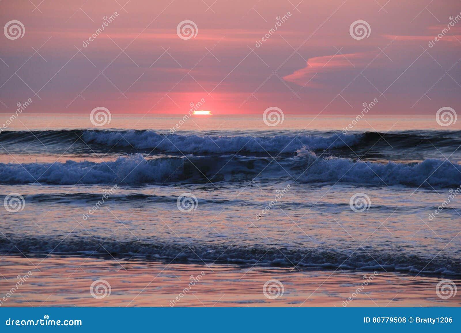 Ursnygg soluppgång över sjösidahorisonten