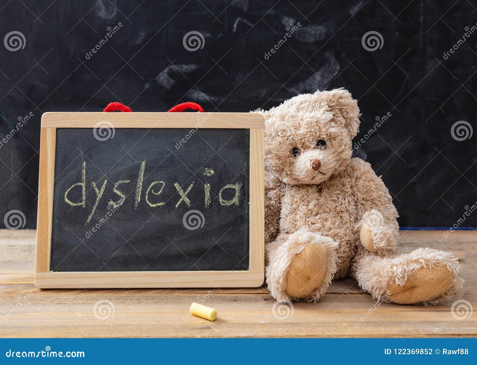 Urso de peluche e um quadro-negro Desenho do texto da dislexia no quadro-negro