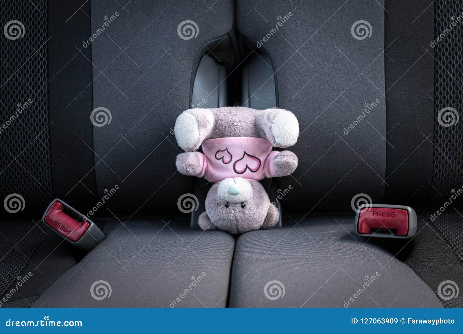 Urso de peluche pequeno que está em sua cabeça em um banco de carro