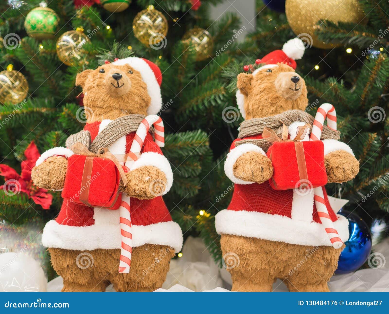 Ursos do brinquedo vestidos como a posição de Santa Clauses contra uma árvore de Natal que guarda caixas de presente