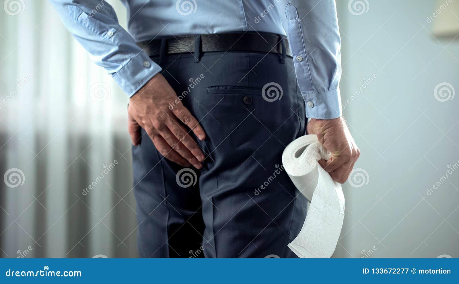 Urzędnik z papierem toaletowym w ręki cierpieniu od hemoroidu bólu, biegunka