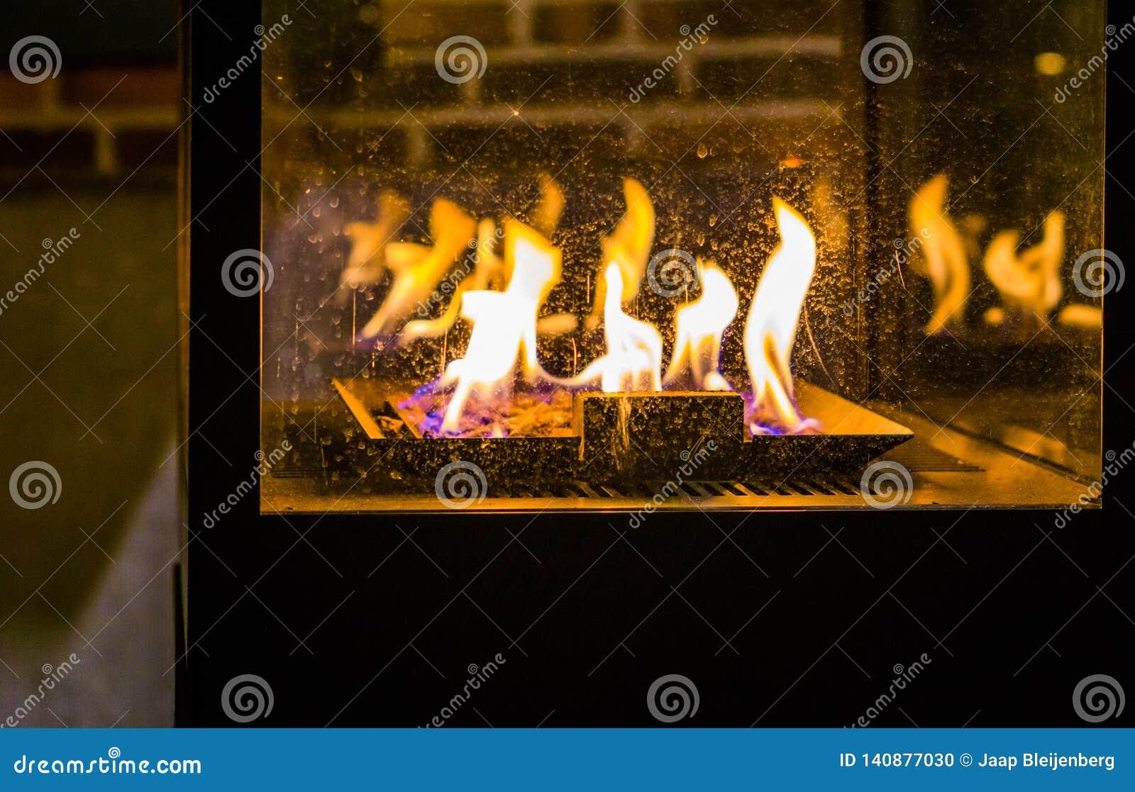 Urze exterior com carvões ardentes e as grandes chamas, estação do inverno, equipamento velho do vintage