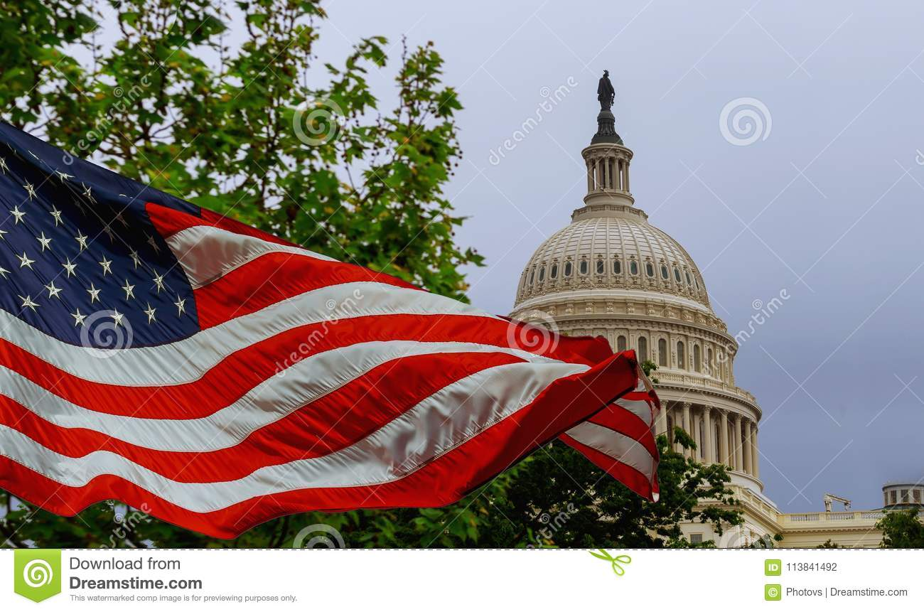 The US Capitol building with a waving American flag superimposed on the sky