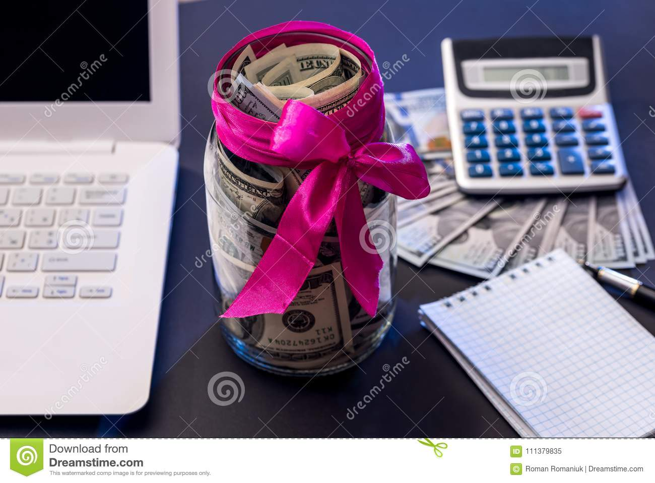Us money with blank open notepad, laptop, calculator. Stock image.