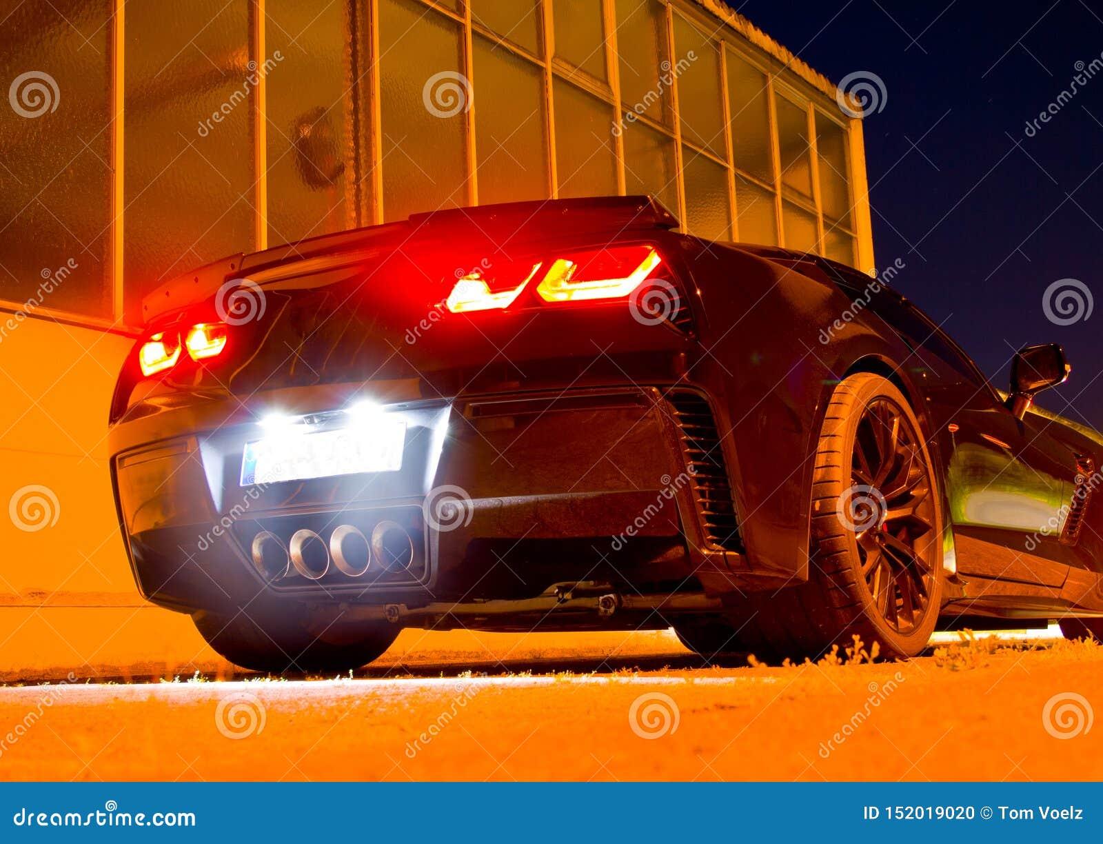 US-Sportauto nachts mit glühenden Rücklichtern